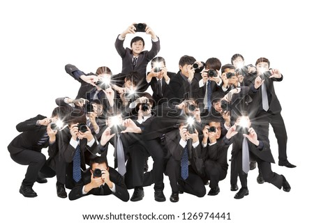 many photographers holding camera pointing to you and isolated on white - stock photo