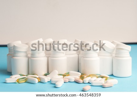 Many pills and tablets isolated on light blue background. Pharmaceutical medicament, cure in container for health. Antibiotic, painkiller closeup. Copy space for text.