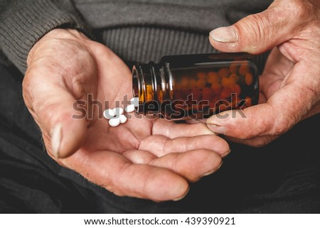 Many pills from a glass bottle in the Senior hands. Painful old age. Caring for the health of the elderly - stock photo