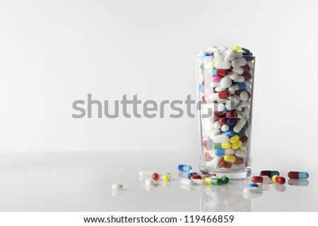 many pills in a glass tumbler, shot on a white background - stock photo