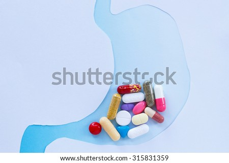 Many pills in stomach.Medicine for treatment concept. - stock photo