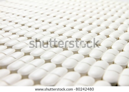 Many pills neatly stored on a flat surface, focused to center - stock photo