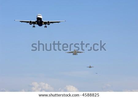 Many planes fly in a row ready to land. - stock photo