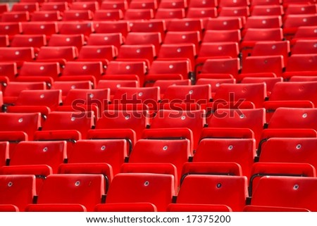 many plastic red seat in deserted stadium