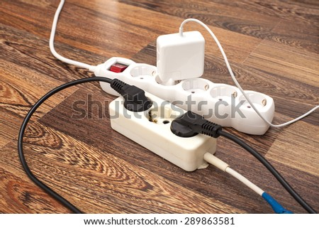Many plugs plugged into electric power bars on floor - stock photo
