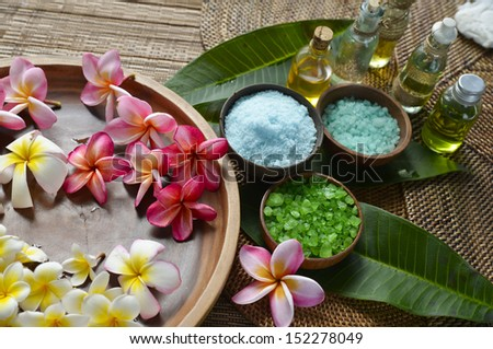Many Plumeria flower in wooden bowl with green leaf, massage oil ,salt in bowl on mat - stock photo