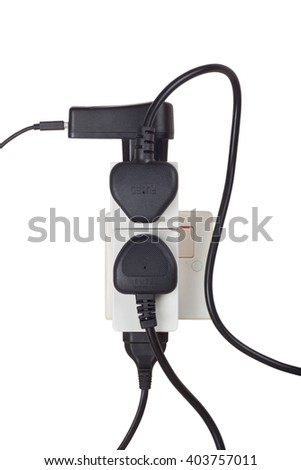 Many power cables plug into a power socket isolated on white background