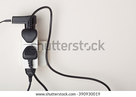 Many power cables plug into an ac power outlet on a wall - stock photo