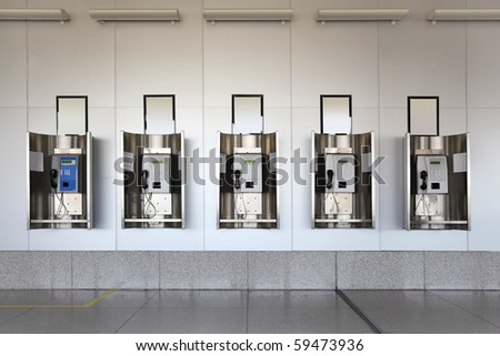 many public phones in big hall with white walls and granite floor - stock photo