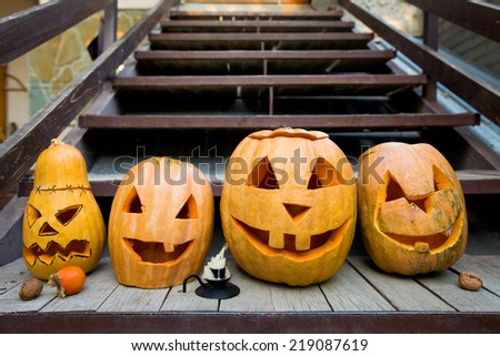 many pumpkins halloveen lie in a row on the wooden porch - stock photo