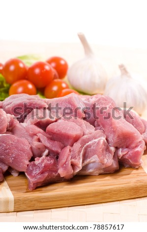 Many raw red pork meat pieces for stew and cherry tomato with garlics lying on board, preparing meal detail, nobody, vertical orientation.