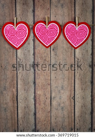 Many red and pink valentine hearts hanging from twine on a wooden plank background