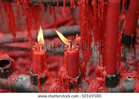 Many red candles with wax dripping in a Buddhist shrine in China.  Two of the candles have flames. - stock photo