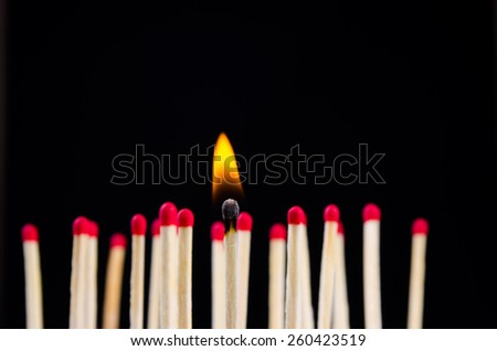 many red matches on black background (one match burns)