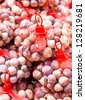 Many red onion with red net  in marketplace. - stock photo