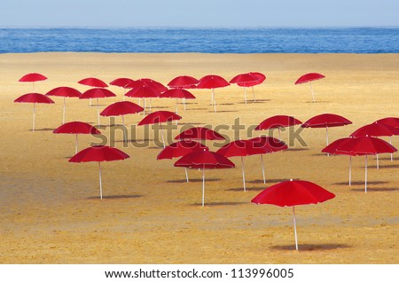 Many red umbrellas stuck in the sand of a beach in a summer morning - stock photo