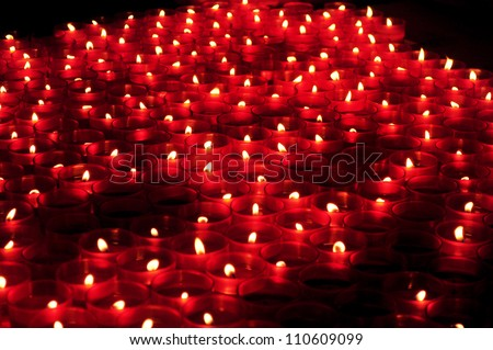 Many red votive candles light the darkness in church - stock photo