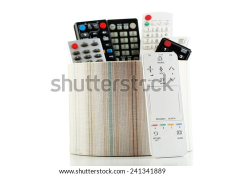 Many remote control devices in container isolated on white - stock photo