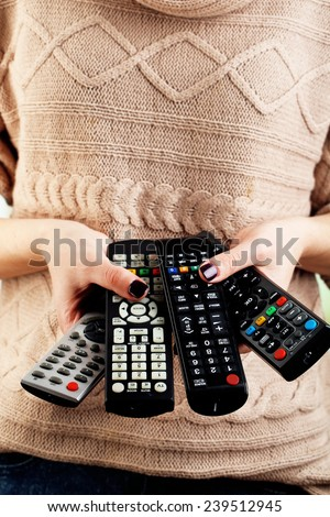 Many remote control devices in in hands - stock photo