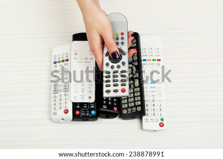 Many remote control devices on table - stock photo
