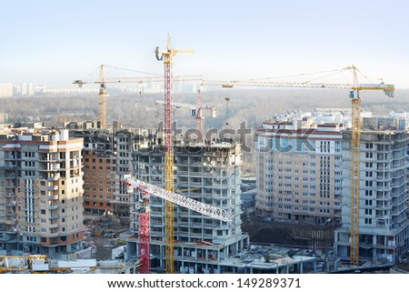 Many residential multi-storey buildings under construction and yellow cranes at sunny day. - stock photo