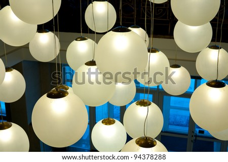 many round ceiling lamps hang at different height
