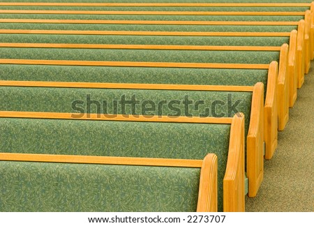 Many rows of empty church pews.