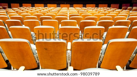 Many rows of wodden chairs at the empty theatre - stock photo