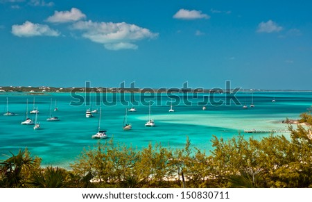 many sailboats and power boats anchored in crystal clear turquoise waters of the bahamas.  copy space available. - stock photo
