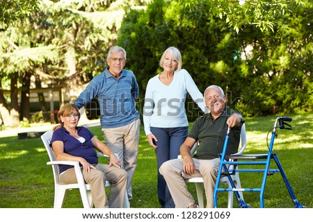 Many senior friends sitting together in a green garden - stock photo
