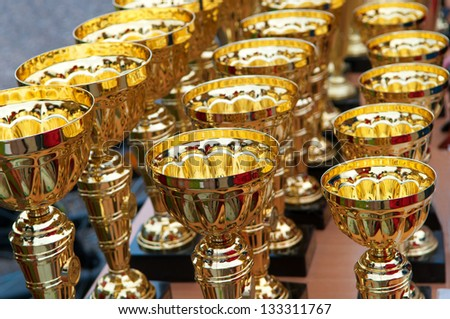 Many shiny gold trophies in a rows