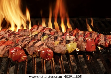 Many Shish Kebab From Different Meat With Pepper And Tomato On The Hot Charcoal BBQ Grill With Bright Flames On The Black Background, Cookout Concept, Close Up, Top View - stock photo