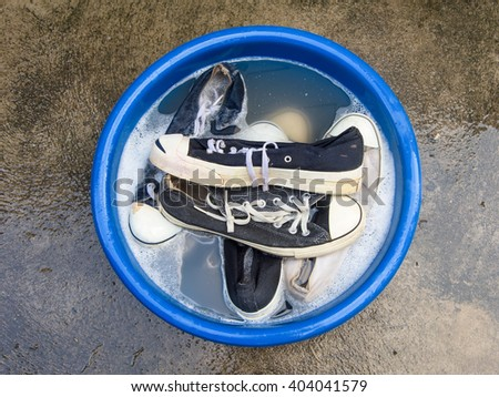 Many Shoes or sneakers in a wash basin with soapy water - stock photo