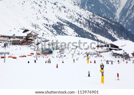Many skiers ride at mountain. Cable car, hotels in Alps at winter day. - stock photo