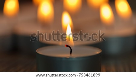 Many small burning candles on a wooden surface