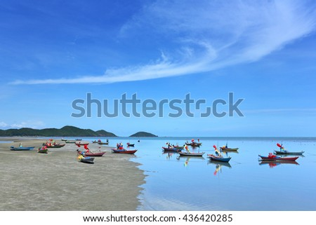 Many small fishing boats in the sea at low tide after the blue sky - stock photo