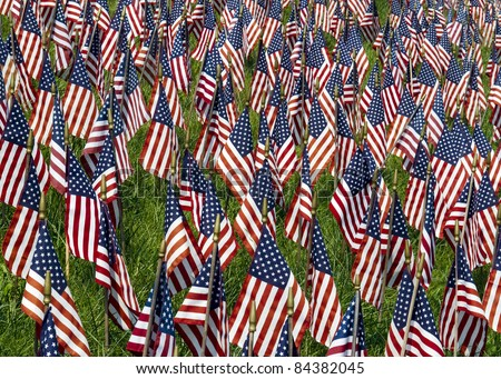 Many small US Flags in a field honoring the fallen of Iraq and Afghanistan. - stock photo