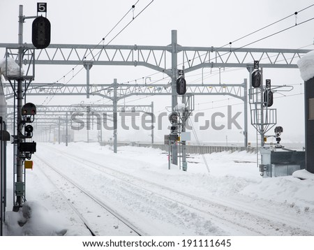 Many snowy railroad tracks in hazy winter - stock photo