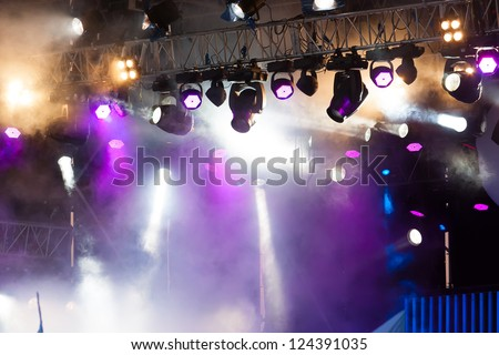 many spotlights that illuminate the stage at a concert with fog