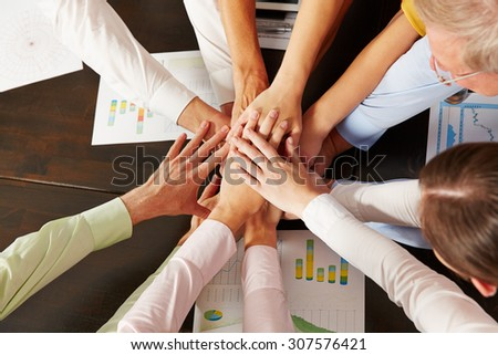 Many stacked hands from above as symbol for cooperation in the office - stock photo