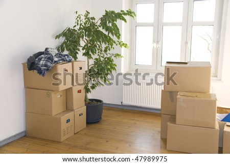many stacked moving boxes in a room - stock photo