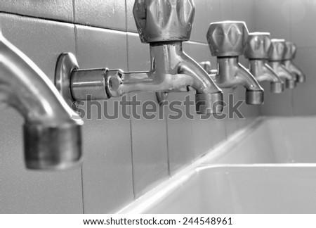 many steel taps in white ceramic sink - stock photo