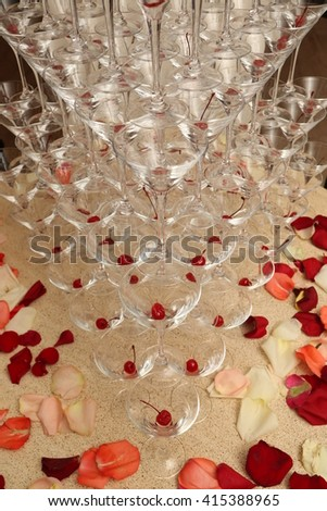Many stemware with cherry on the table rose petals - party background - stock photo