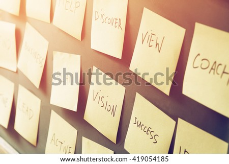 many sticky notes attached to blackboards with handwriting text, business and coaching concet - stock photo