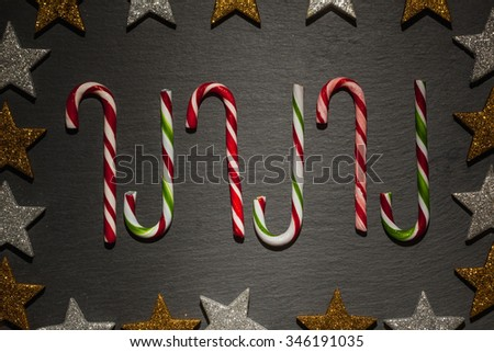 Many striped candy canes on dark slate background with frame of golden and silver stars, Christmas decoration. - stock photo