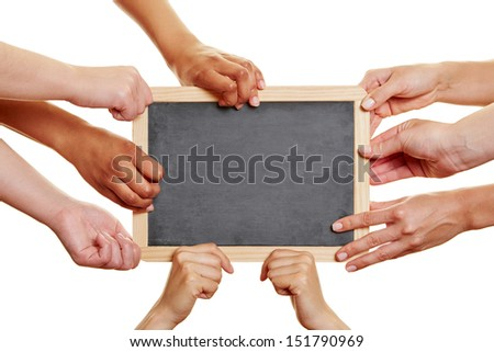 Many students holding empty blackboard in their hands - stock photo