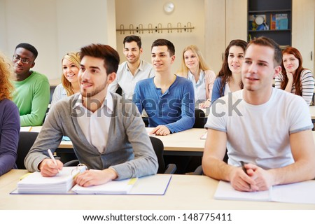 Many students in seminar studying and listening in university classroom - stock photo