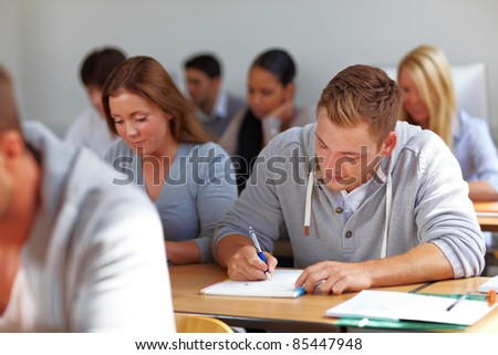 Many students learning in class at university - stock photo