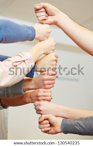 Many students stacking their fists as teamwork symbol - stock photo