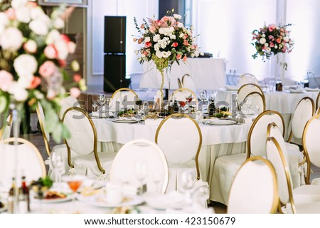 Many tables with flowers for the wedding guests - stock photo